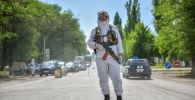 Сотрудник правоохранительных органов на санитарном посту в селе Киршелк Чуйской области