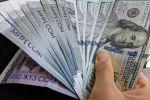 Сомовые и долларовые купюры в руках человека. Архивное фото