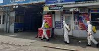 Сотрудники МЧС во время дезинфекции на рынке Орто-Сай