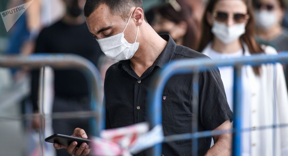Люди в медицинских масках во время теплой погоды. Архивное фото