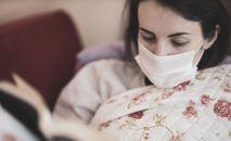 Девушка в медицинской маске читает книгу. Архивное фото