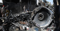 Сотрудники службы безопасности стоят рядом с обломками самолета на месте происшествия после падения самолета  в Карачи. Архивное фото
