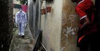 Медицинский работник идет по району трущоб во время проверки на наличие коронавирусной болезни в Мумбаи (Индия)