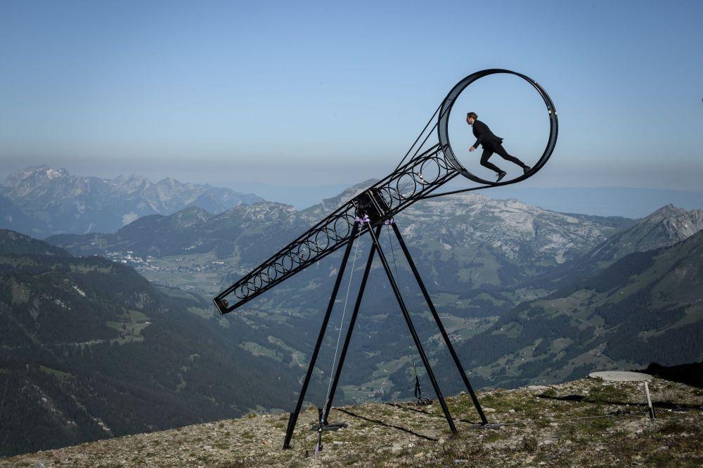 Акробат Рамон Катринер исполняет трюк на аттракционе Колесо смерти, установленном над пропастью в Швейцарских Альпах.