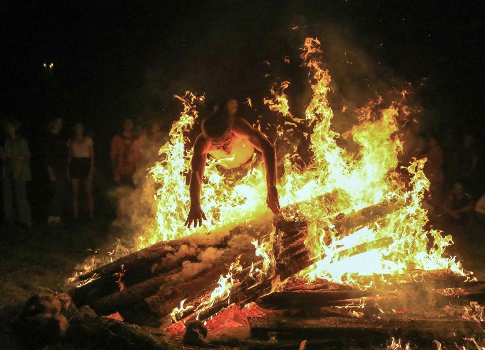 Мужчина прыгает через огонь во время празднования летнего солнцестояния в Литве. 23 июня 2020 года