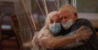 Женщина обнимает своего отца через полиэтиленовую пленку в доме престарелых в Барселоне. Архивное фото
