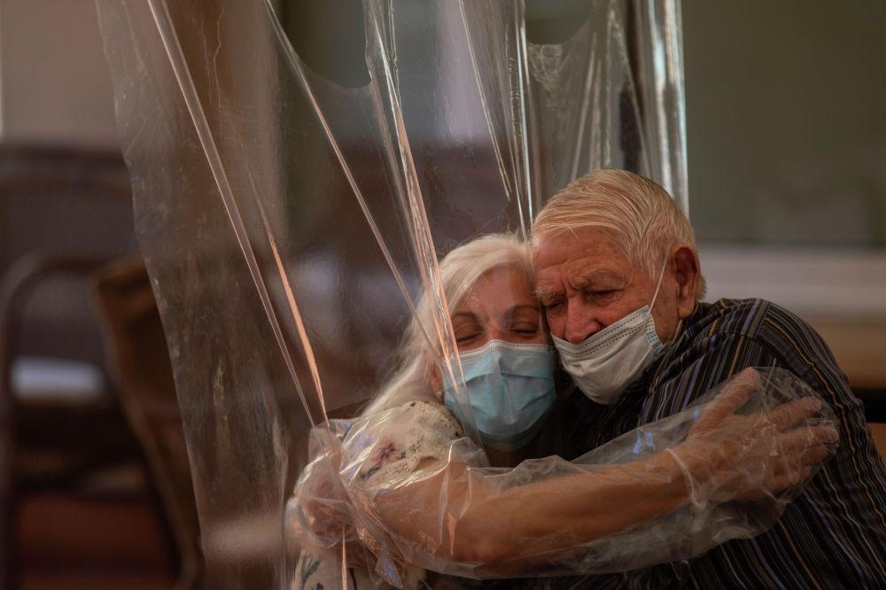 Женщина обнимает своего отца через полиэтиленовую пленку в доме престарелых в Барселоне (Испания). 22 июня 2020 года