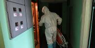 Медицинских работник в защитном костюме заходит в квартиру пациента. Архивное фото