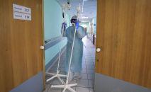 Медицинский работник несет штативы для капельниц. Архивное фото