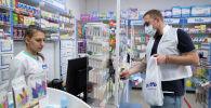 Мужчина покупает лекарства в аптеке. Архивное фото