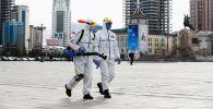 Люди в защитных костюмах проводят дезинфекцию на площади Улан-Батора, Монголия
