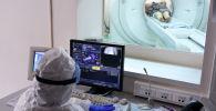 Врач смотрит показания аппарата компьютерной томографии. Архивное фото