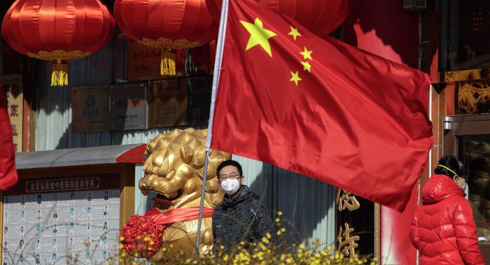 Человек в маске возле флага Китая в Пекинской больнице народной медицины. Архивное фото