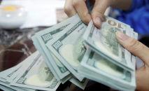 Сотрудник банка считает банкноты в долларах США. Архивное фото