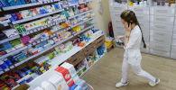 Фармацевт возле стеллажей с лекарствами в аптеке. Архивное фото