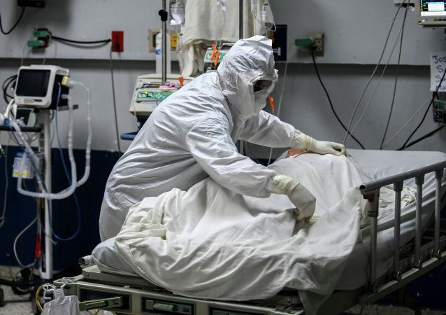 Медицинский работник поправляет постель пациента с коронавирусом