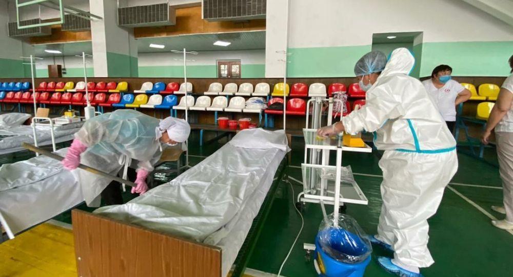 Медицинские работники готовят койки на дневном стационаре в одном из спортзалов Бишкека