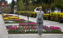 Девушка фотографирует цветы на улице. Архивное фото