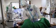 Доктор коронавируска чалдыккан бейтапты текшерүүдө. Архивдик сүрөт