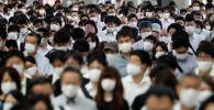 Люди в защитных масках в час пик на железнодорожной станции