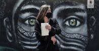 Женщина в маске на фоне распространения нового коронавируса проходит мимо граффити. Архивное фото
