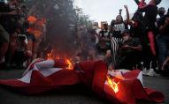 Протестующие и журналисты собрались вокруг горящего флага Соединенных Штатов в Вашингтоне в День независимости США