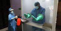 Медицинский работник дезинфицирует перчатки другого мед работника