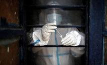 Медицинский работник в средствах индивидуальной защиты (СИЗ) помещает образец мазка в пробирку