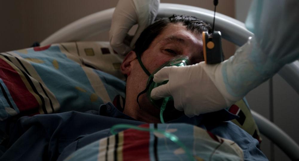 Кычкылтек маскасын бейтапка кийгизген врач. Архивдик сүрөт