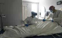 Медицинский персонал в полном СИЗ обертывает покойного пациента. Архивное фото