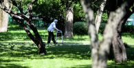 Пожилая женщина во время прогулки в парке. Архивное фото