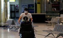 Пассажир в защитной маске с своим багажом в международном аэропорту. Архивное фото