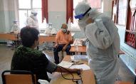 Медик измеряет женщине артериальное давление в одном из дневных стационаров в Бишкеке