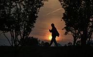 Мужчина в лицевой маске гуляет на закате в парке. Архивное фото