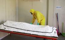 Медик  у тела пациента, который умер в отделении инфекционных заболеваний. Архивное фото