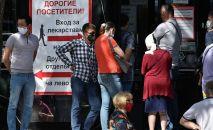 Люди стоят в очереди за лекарствами у аптеки. Архивное фото